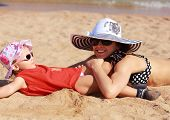 Happy Mother And Kid Lying On The Sand On Beach In Hat And Glasses