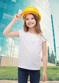 construction and people concept - smiling little girl in protective helmet looking up