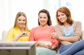 home, technology and friendship concept - three smiling teenage girl watching tv at home and eating