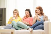 home, technology and friendship concept - three sad teenage girl watching tv at home and eating popc