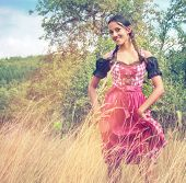 Young woman in traditional Bavarian dirndl walking alone in the field