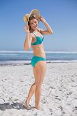 Slender woman in bikini on beach wearing sunhat smiling at camera on a sunny day