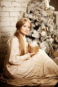 Young luxury vintage woman near Christmas tree with gift. Beautiful young girl celebrates Christmas in vintage style.