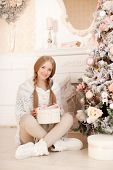 Beautiful young woman in white near the Christmas tree. Beautiful girl celebrates Christmas
