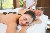 Calm friends lying on massage tables with hot stones on their backs in the health spa