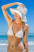 Smiling blonde in white bikini and sunhat on the beach on a sunny day