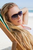 Gorgeous blonde in sunglasses sitting at the beach on a sunny day