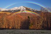Spring landscape with the last snow. Rainbow over mountains