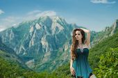 Beauty Girl Outdoors Enjoying Nature Over Mountain Landscape. Beautiful Teenage Model In Long Dress