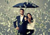 foto of rain  - smiley successful couple with umbrella standing under money rain - JPG