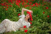 Beautiful  Woman Sitting In The Poppy Flower
