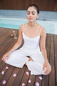 Peaceful brunette in white sitting in lotus pose surrounded by petals in health spa