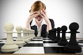 Composite image of redhead businesswoman with head in handswith chessboard