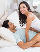 Attractive brunette straddling boyfriend on bed at home in bedroom