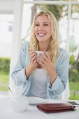 Pretty blonde sitting at table having coffee smiling at camera on the cafe terrace on sunny day