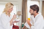 Couple having breakfast in their bathrobes at home in the living room