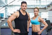 Bodybuilding man and woman frowning at camera at the gym