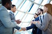 image of applause  - Group of business people congratulating their colleagues with striking grand deal - JPG