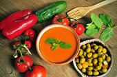 a bowl with spanish gazpacho, some vegetables to prepare it such as tomato, red pepper and cucumber,