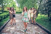 foto of envy  -  joyful girl with the mobile phone and group of envying girls - JPG