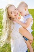 beautiful young woman with her daughter outdoor on a summer day
