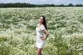Young beautiful woman in a dress standing in a field of chamomile