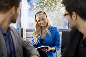 Portrait of beautiful young blonde businesswoman flirting with male colleagues.