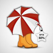 Monsoon 50% discount sale tag on umbrella and boots on grey background.