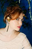 Romantic portrait of a beautiful woman with red hair and flowers in her hairstyle, wearing diamond e