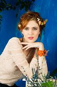 portrait of a beautiful woman with red hair in braided hairstyle and flowers in her hair. wearing le