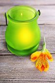 Bright icon-lamp with flower on wooden background