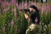 pic of terrorist  - Man with gun among flowers - JPG