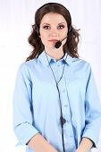 Young business woman with headset in room