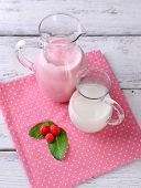 Glass jug of milk cocktail with raspberry taste on wooden table, on light background