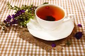 Cup of fresh herbal tea on table