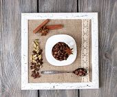 Wooden frame with white mug, coffee grains and spices on wooden background