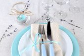 Dining table setting with lavender flowers on light tablecloth background
