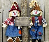Blank rustic wood sign hanging on tree next to boy and girl scarecrows