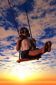 Girl riding on a swing.