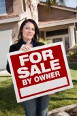 Hispanic Woman Holding For Sale By Owner Real Estate Sign In Front Of House poster