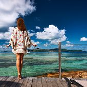 Woman on a tropical beach jetty at at Seychelles, La Digue.