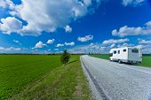 image of camper-van  - Camper van parked on the roadside of an open landscape on a beautiful sunny day with fluffy clouds - JPG