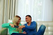 Beautiful couple bickering to change tv channel on remote control