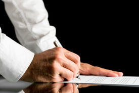 picture of reflections  - Close-up of the hands of a man wearing white shirt while signing with a pen an official paper document or agreement placed on a black reflective table with copy space on black background. ** Note: Shallow depth of field - JPG
