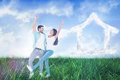 Happy casual couple cheering together against field of grass under blue sky