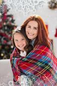 Festive mother and daughter wrapped in blanket against snowflake frame