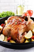 Delicious baked chicken on table on brick wall background