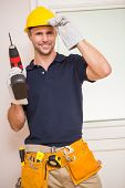 Construction worker posing while holding power tool in a new house