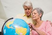 Senior couple choosing a travel destination at home in the kitchen