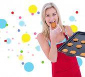 Happy blonde eating hot cookies against dot pattern